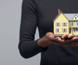 Cropped shot of a woman holding a miniature house
